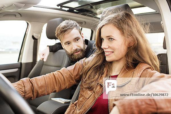 Lächelnde junge Frau beim Autofahren mit Mann auf dem Rücksitz
