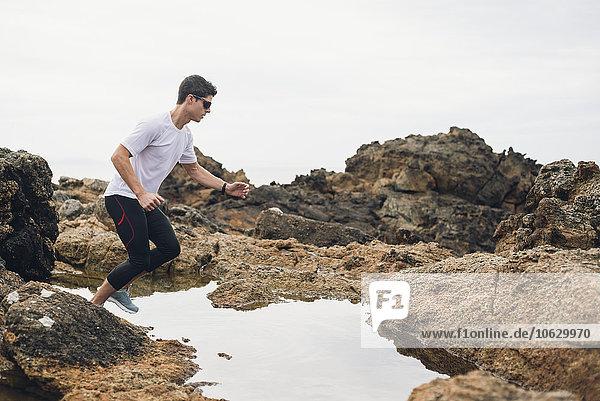 Spanien  Ferrol  Jogger bereit zum Sprung über Wasser an der Küste