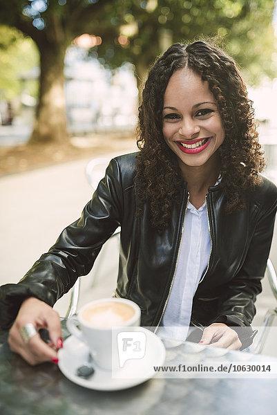 Porträt einer lächelnden jungen Frau mit einer Tasse Kaffee