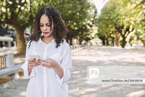 Porträt einer jungen Frau mit Blick auf ihr Smartphone