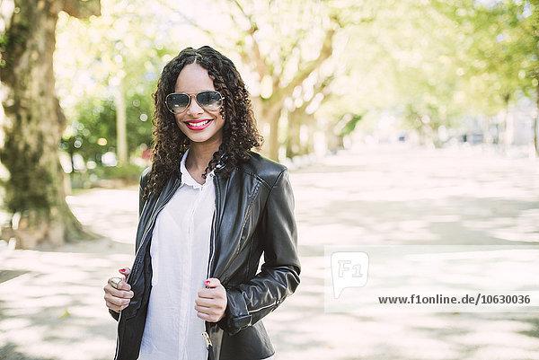 Porträt einer lächelnden Frau mit Sonnenbrille und Lederjacke im Park