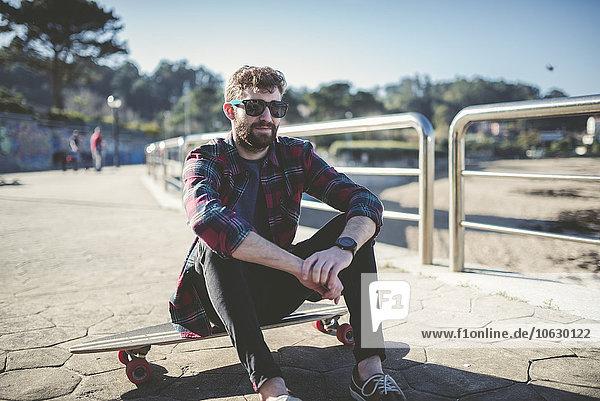 Spanien  La Coruna  Porträt eines Hipsters mit Sonnenbrille auf dem Longboard