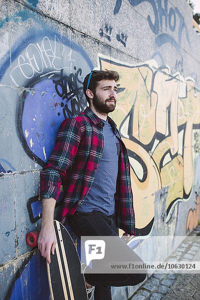 Spanien  La Coruna  Porträt eines an die Wand gelehnten Hipsters mit seinem Longboard