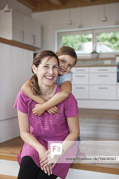Mutter und Tochter lächelnd in der Küche sitzend