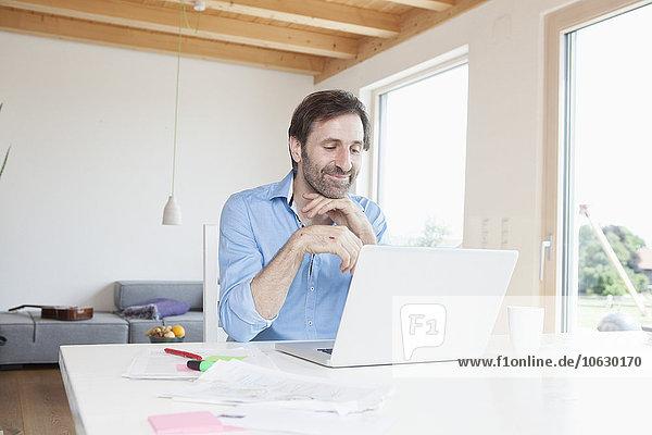 Erwachsener Mann  der von zu Hause aus mit dem Laptop arbeitet.