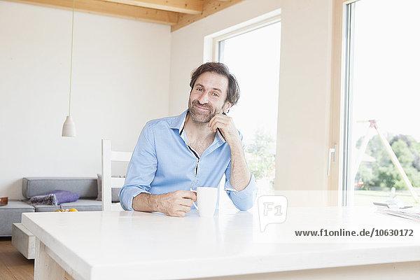 Der reife Mann trinkt zu Hause Kaffee und sieht zufrieden aus.