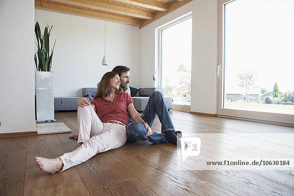 Ein reifes Paar  das auf dem Boden sitzt und glücklich lächelt.