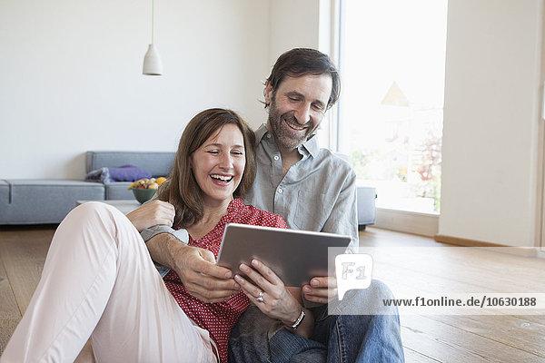 Erwachsenes Paar auf dem Boden sitzend  mit digitalem Tablett