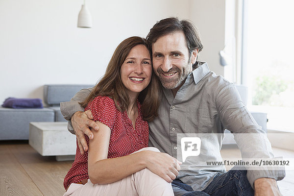 Erwachsenes Paar auf dem Boden des Wohnzimmers sitzend