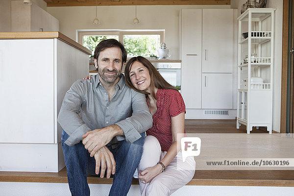 Erwachsenes Paar auf dem Boden sitzend  Vorderansicht