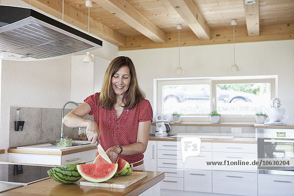 Mature woman in kitchen cutting water melon