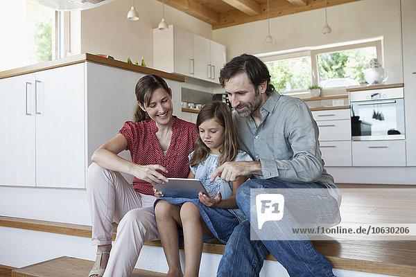 Fröhliche Familie auf Küchenstufen sitzend  Tochter mit digitalem Tablett