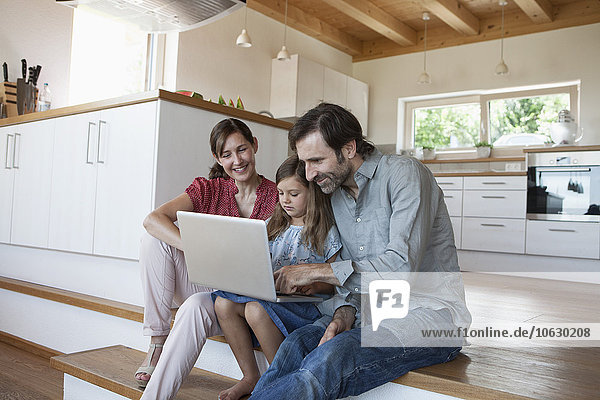Glückliche Familie sitzend auf Küchenstufen  Tochter mit Laptop
