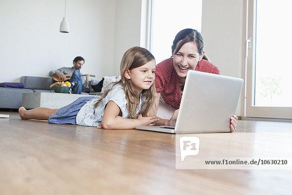 Mutter und Tochter liegen auf dem Boden mit Laptop  Vater macht Musik im Hintergrund