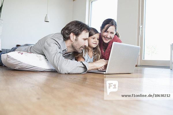Glückliche Familie auf dem Boden liegend  mit Laptop
