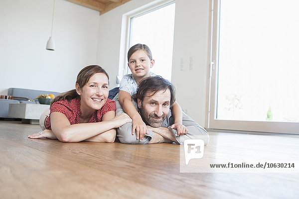Glückliche Familie auf dem Boden liegend  lächelnd