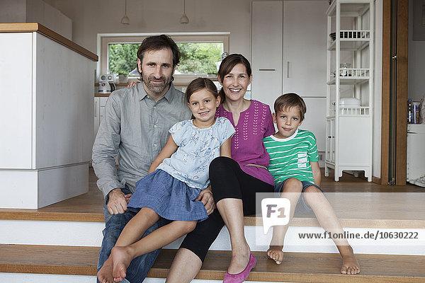 Fröhliche Familie sitzt auf Küchenstufen