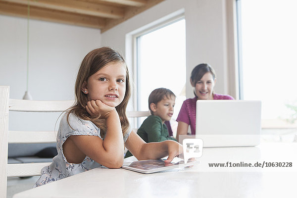 Kleines Mädchen mit digitalem Tablett  Mutter und Bruder mit Laptop im Hintergrund