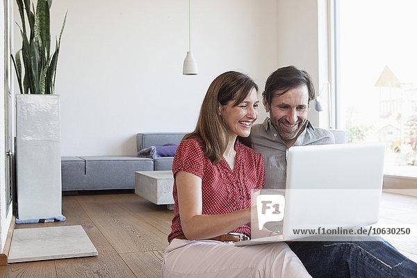 Erwachsenes Paar  das auf dem Boden sitzt  mit Laptop