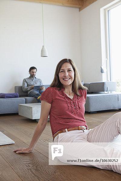 Reife Frau lächelnd auf dem Boden im Wohnzimmer sitzend  Mann mit digitalem Tablett im Hintergrund