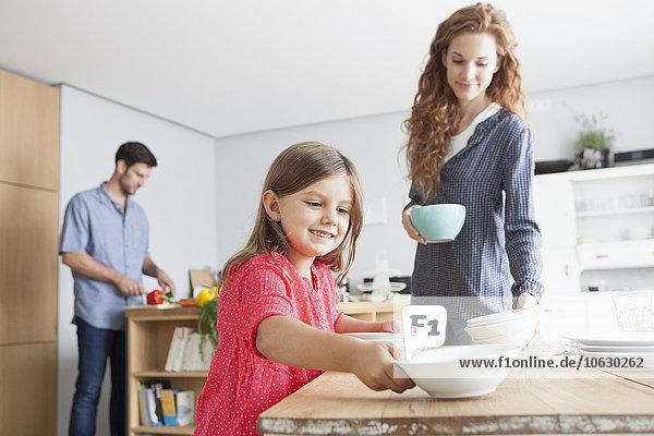 Lächelndes kleines Mädchen deckt den Tisch in der Küche mit ihren Eltern im Hintergrund.
