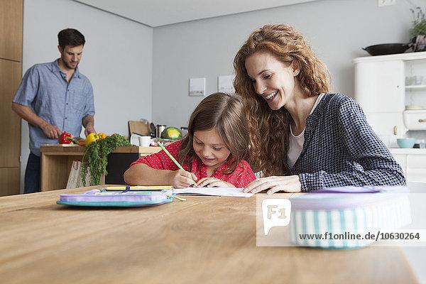 Kleines Mädchen bei den Hausaufgaben am Küchentisch