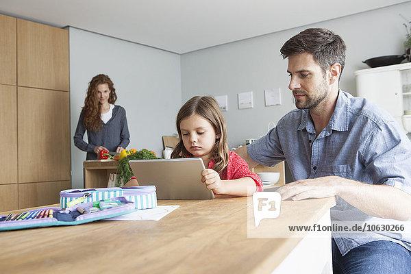 Kleines Mädchen und ihr Vater sitzen am Küchentisch und schauen auf ein digitales Tablett.