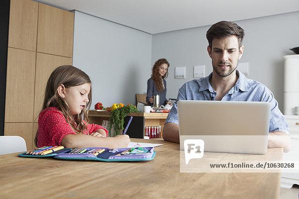 Mann sitzt am Küchentisch mit Laptop  während seine kleine Tochter malt.