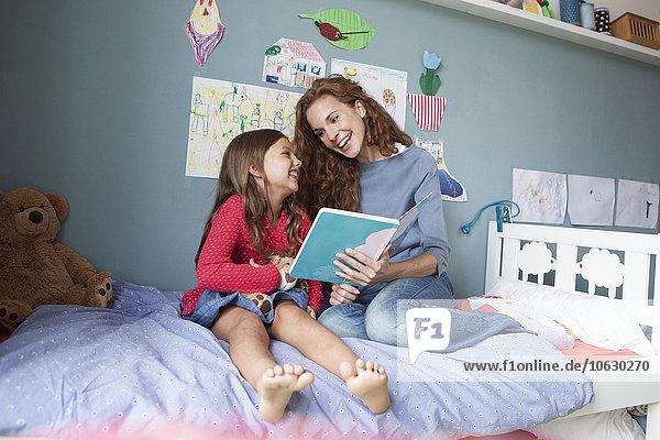 Mutter und kleine Tochter sitzen zusammen auf dem Bett im Kinderzimmer mit Buch