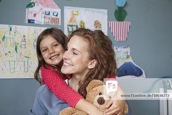 Porträt der glücklichen Mutter und ihrer kleinen Tochter im Kinderzimmer