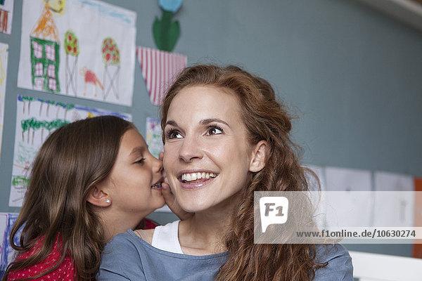 Kleines Mädchen flüstert ihrer Mutter ein Geheimnis zu.