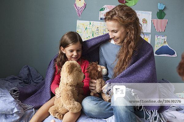 Mutter und Tochter sitzen auf dem Bett im Kinderzimmer und spielen mit Plüschtieren.