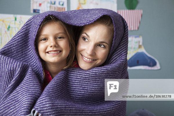 Porträt von Mutter und kleiner Tochter mit Wolldecke