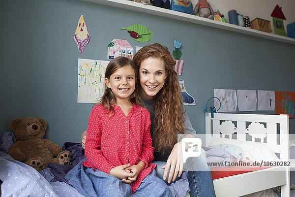 Porträt der Mutter und der kleinen Tochter  die nebeneinander auf dem Bett im Kinderzimmer sitzen.