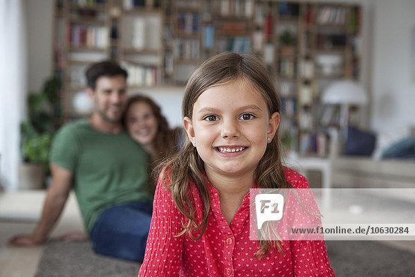 Porträt des lächelnden Mädchens und ihrer Eltern im Hintergrund im Wohnzimmer