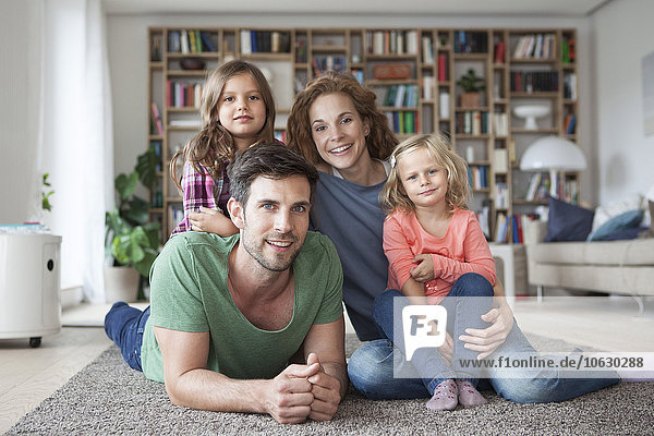 Familienporträt der Familie mit zwei kleinen Mädchen auf dem Boden des Wohnzimmers
