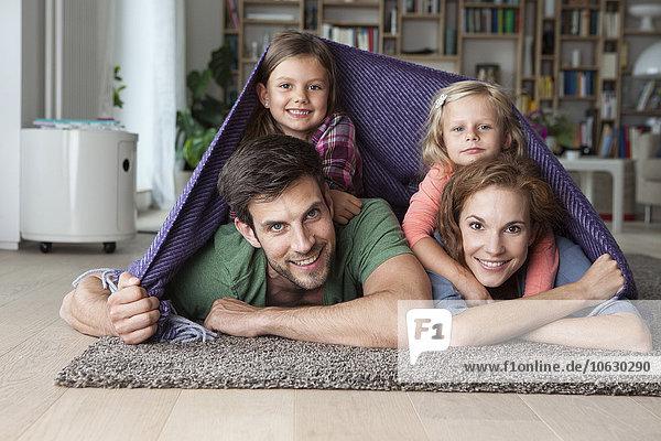 Porträt eines Paares mit ihren kleinen Töchtern  die zusammen auf dem Boden des Wohnzimmers liegen und von einer Decke bedeckt sind.