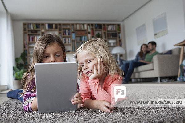 Zwei kleine Schwestern liegen auf dem Boden im Wohnzimmer mit digitalem Tablett  während ihre Eltern im Hintergrund sitzen.
