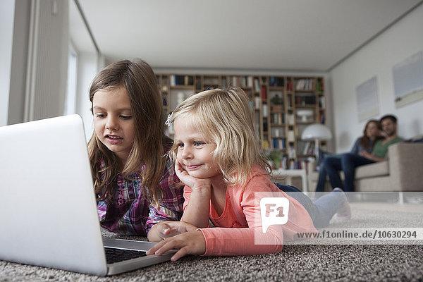 Zwei kleine Schwestern liegen auf dem Boden im Wohnzimmer mit Laptop  während ihre Eltern im Hintergrund sitzen.