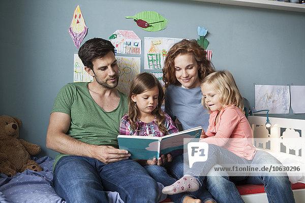 Paar und kleine Töchter sitzen zusammen auf dem Bett im Kinderzimmer und lesen ein Buch.