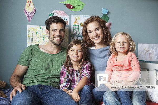 Familienbild eines Paares mit ihren kleinen Töchtern  die zusammen auf dem Bett im Kinderzimmer sitzen.