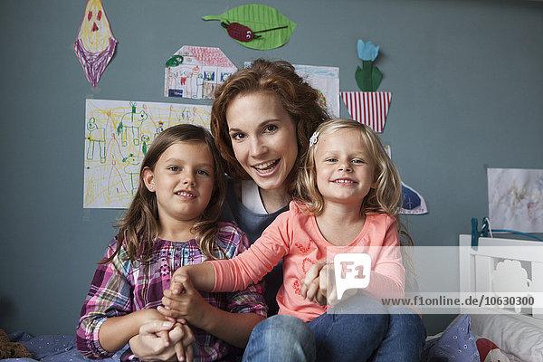 Gruppenbild Frau mit ihren kleinen Töchtern im Kinderzimmer