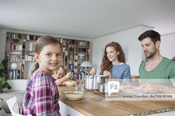 Porträt eines kleinen Mädchens  das mit seinen Eltern und seiner Schwester am Esstisch sitzt.