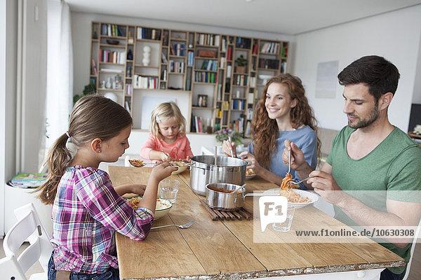 Kleines Mädchen am Esstisch mit Eltern und Schwester beim Spaghettiessen