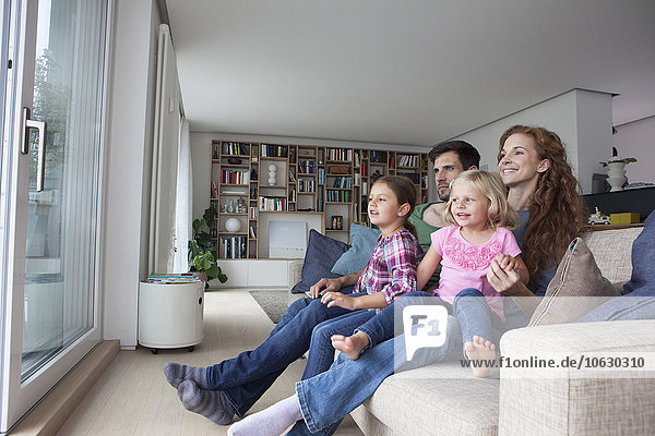 Paar und zwei kleine Mädchen auf der Couch im Wohnzimmer mit Blick durch die Terrassentür