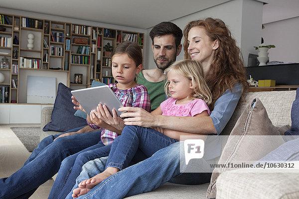Paar sitzend mit ihren zwei kleinen Töchtern auf der Couch im Wohnzimmer mit Blick auf ein digitales Tablett.