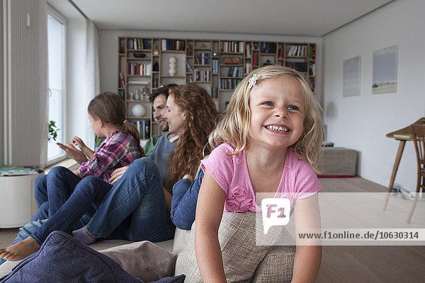 Porträt eines lächelnden kleinen Mädchens auf der Rückenlehne der Couch mit ihrer Familie im Hintergrund.