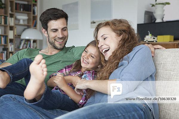 Glückliches Paar und kleine Tochter auf der Couch zu Hause