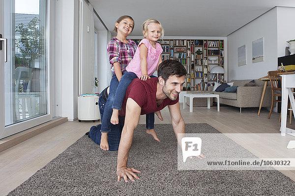 Mann  der mit seinen kleinen Töchtern im Wohnzimmer spielt.