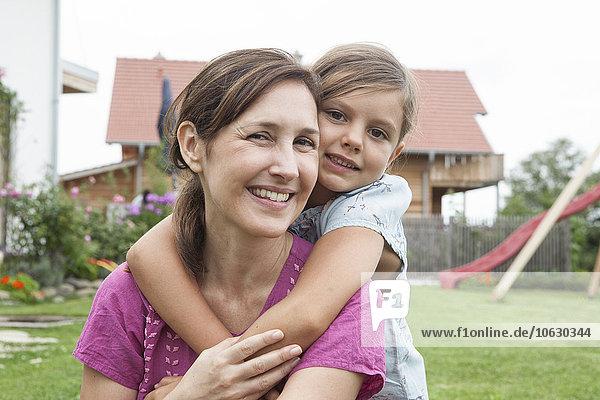 Porträt einer lächelnden Mutter  die ihre Tochter huckepack im Garten trägt.